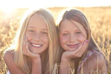 2 Mädchen vor Sonne im Getreide