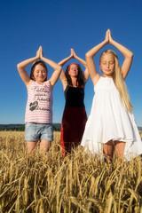 Frau mit zwei Mädchen beim Yoga im Feld
