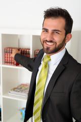 Geschäftsmann im Büro nimmt ein Buch aus dem Regal