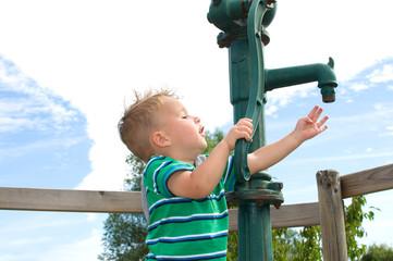 Kleiner Junge spielt an der Pumpe