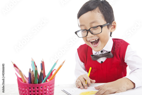 Cheerful pupil drawing with crayons