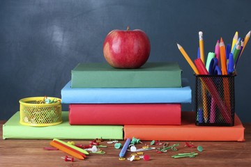 Composition of books, stationery and an apple