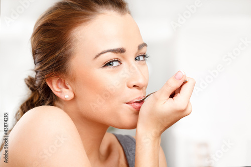 Close-up portrait of an attractive young woman eating yogurt
