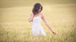 Young beautiful woman in a wheat field with white dress.