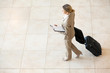 young businesswoman walking at airport with luggage