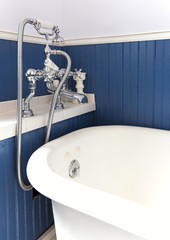 White tub with antique hardware and blue wood wall.