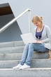 Student girl on stairs with laptop smiling