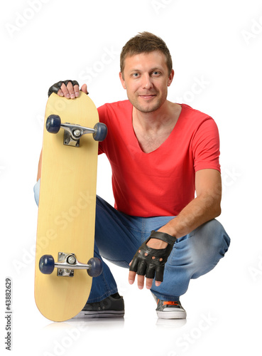 Young man with skateboard on white background