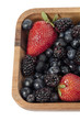 strawberries blueberries and blackberries in wooden bowl