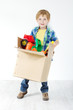 Child holding cardboard box packed with toys. Moving and growing