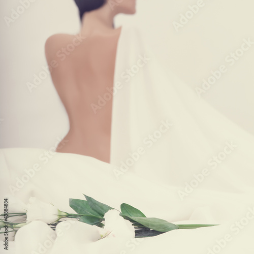 portrait of a sensual woman with flowers on a white bed