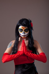 Praying woman with sugar skull make-up