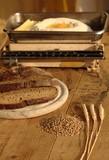 Getreide mit Brot Eier Mehl und alter Wage auf Holzplatte poster