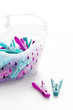 coloured plastic clothes pegs and basket