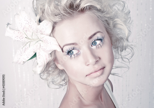 Beautiful young female portrait with original make up and flower