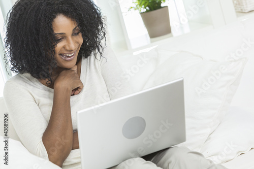 African American Woman Using Laptop Computer At Home on Sofa