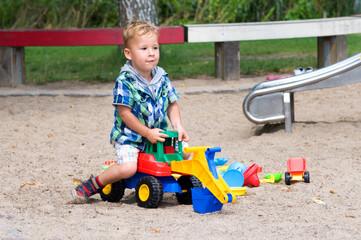 Kleinkind mit Bagger im sand