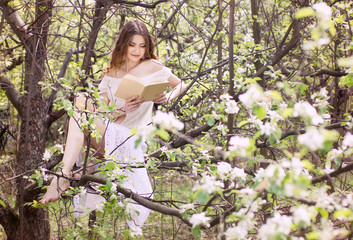 young girl reading book in garden