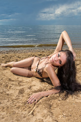 The beautiful brunette lays on a beach