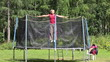 Woman jumping on a trampoline, the background of the forest