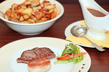 Rinder- und Schweinesteak mit Bratkartoffeln und Soße