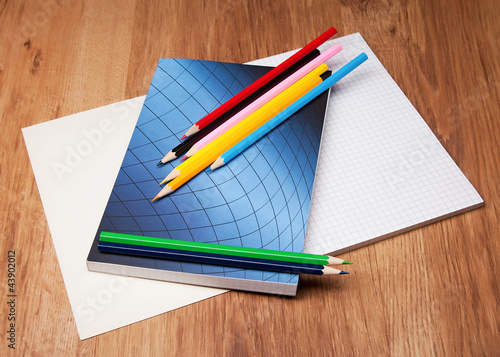 pencils and notebook on wooden table