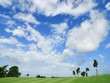 time lapse shot of green golf course with could and blue sky