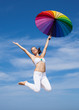 Woman jumping with iridescent umbrella