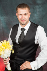 young groom with a bouquet of yellow lilies in studio