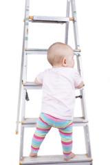 studio shot of a baby girl climbing up a ladder