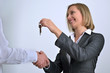 Successful businesswoman giving keys to businessman