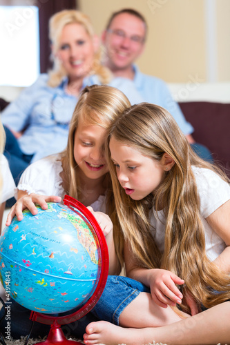 Family at home, the children playing with a globe