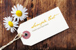 Blank Label with Daisies on a Wooden Background