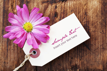 Blank Label with a Pink Flower on a Wooden Background
