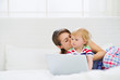 Young mother kissing her modern baby working on laptop