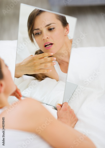 Young woman laying on bed and checking face in mirror