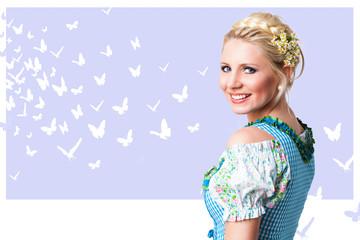 junge blonde Frau in Trachtenmode vor Schmetterlingshintergrund
