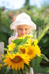 kleines Mädchen verschenkt Sonnenblumen