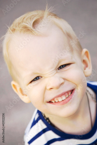 smiling little boy with blond hair and blue eyes close up.