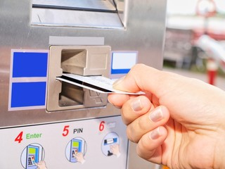 Person inserting a card into a vending machine