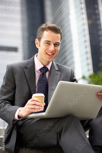 Businessman Working On Laptop Outside Office With Coffee