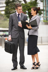 Businessman And Businesswoman Discussing Document In Street Hold