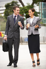 Businessman And Businesswoman Walking Along Street With Coffee