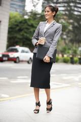 Businesswoman Walking Along Street Holding Takeaway Coffee