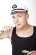 Young attractive man with sailor hat eating onion