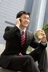Chinese Businessman Talking On Mobile Phone With Takeaway Coffee