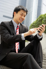 Chinese Businessman Dialling On Mobile Phone Outside Office