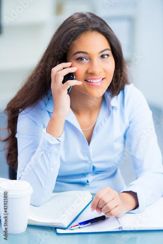 junge frau sitzt am schreibtisch und telefoniert