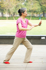 Senior Chinese Woman Doing Tai Chi In Park