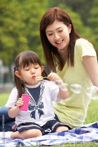 Chinese Mother With Daughter In Park Blowing Bubbles
